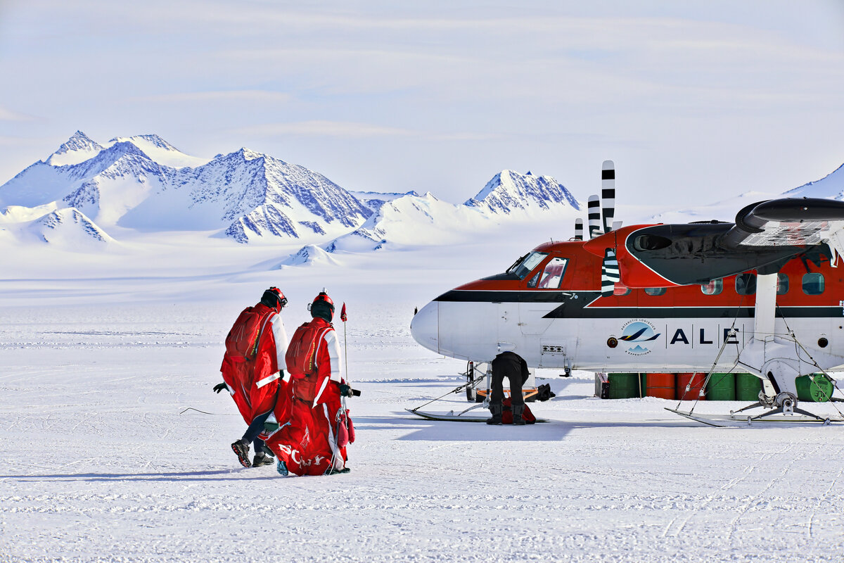 Wingsuiters walk towards the Twin Otter