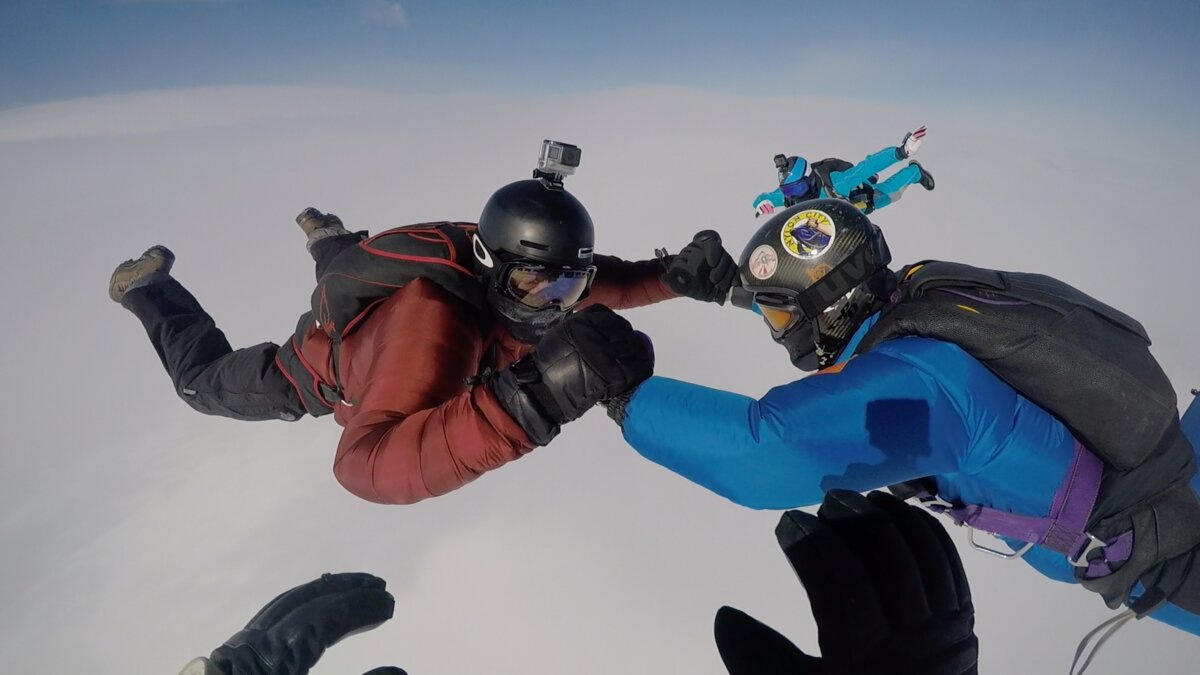Four skydivers attempt to lock hands during a jump