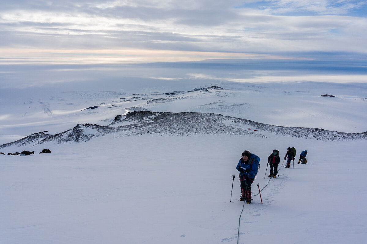 Rope team climbs snow slope en route to summit