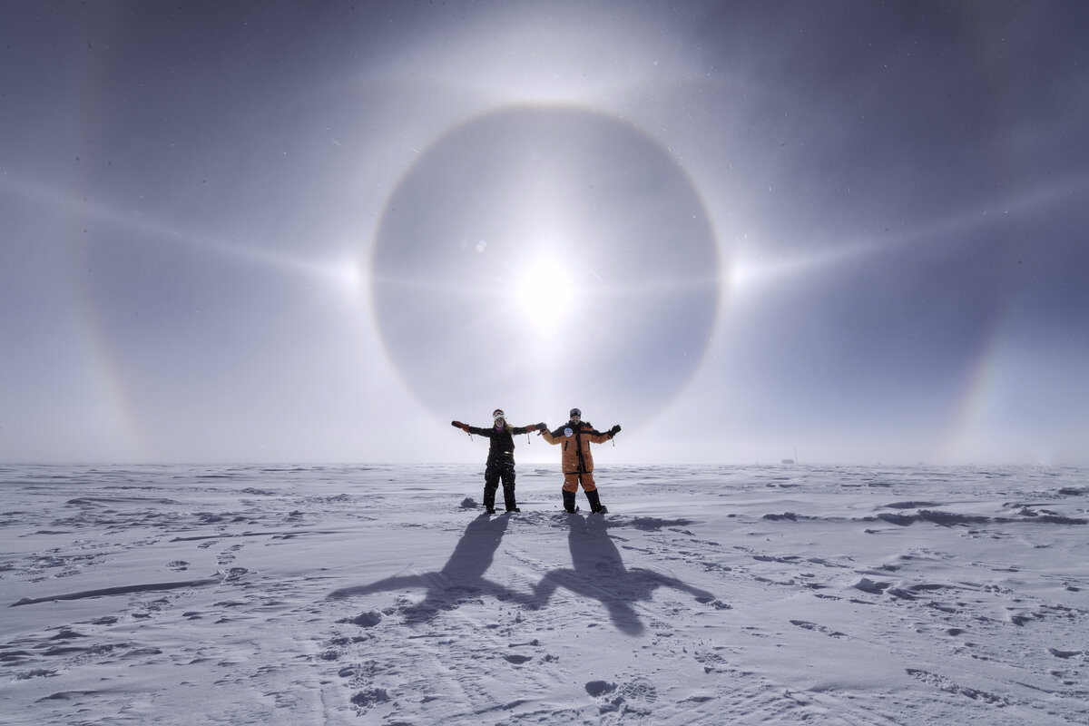 Two guests celebrate a stunning solar halo at the South Pole