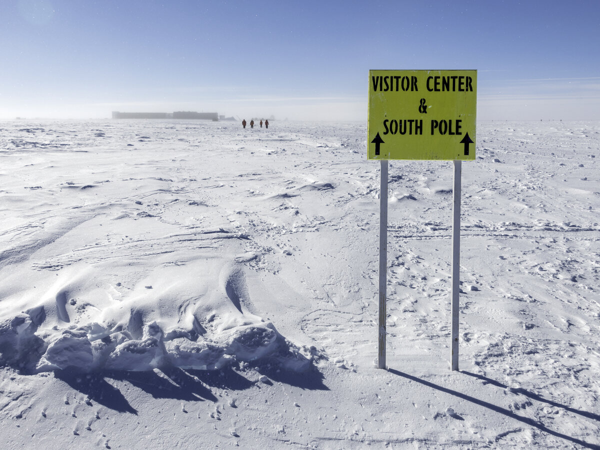 A sign pointing the way to the Visitor Center and South Pole markers