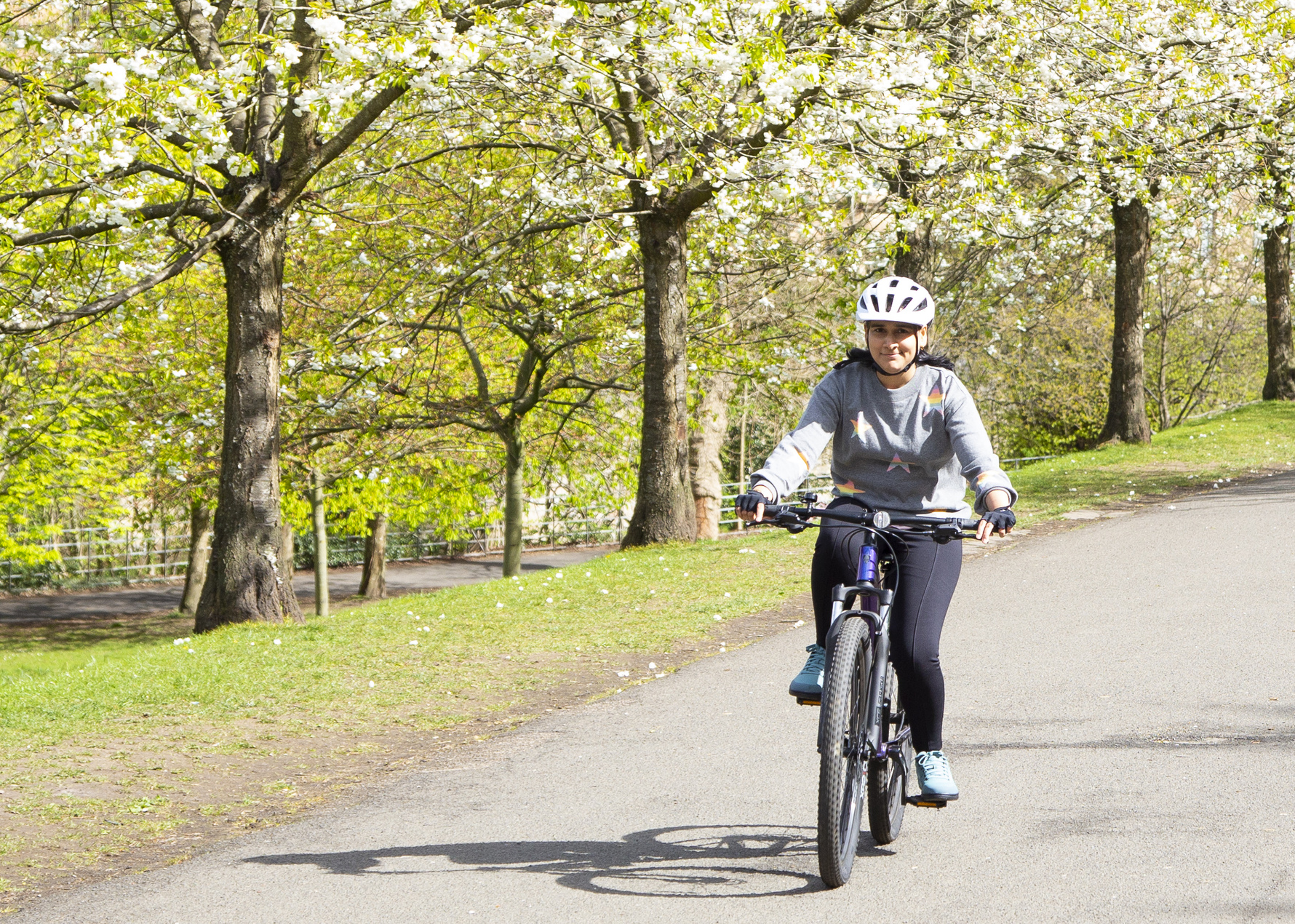 a woman cycling in the park with cherry blossom trees in the background
