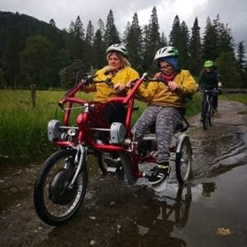 a woman and a young boy riding an adaptive bike together near a forest