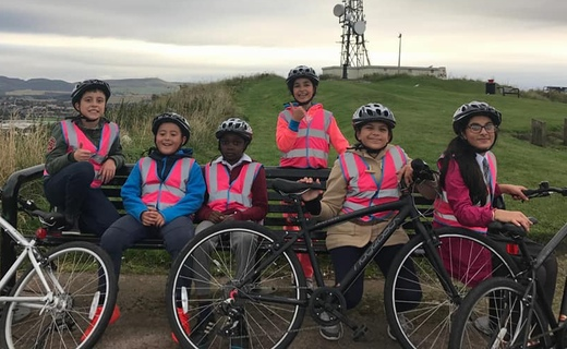 a group of children with bikes sitting on a bench on top of a hill