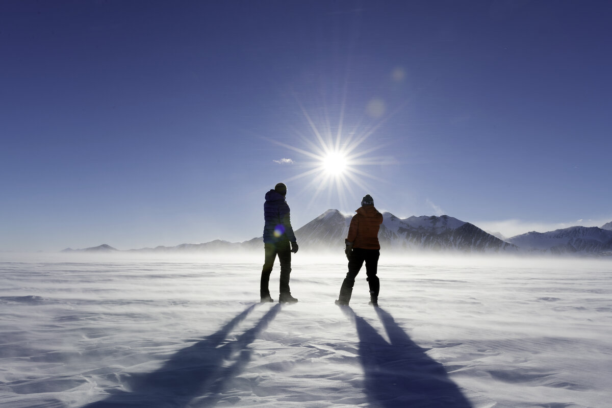 Two people stand and look at the sun over mountains as seen from the 10k loop in the early 'morning' hours outside of Union Glacier Camp.