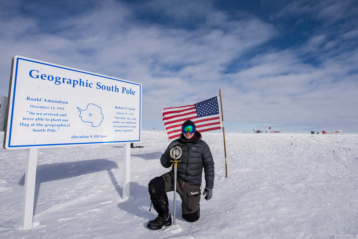 Guest kneels by the Geographic South Pole marker