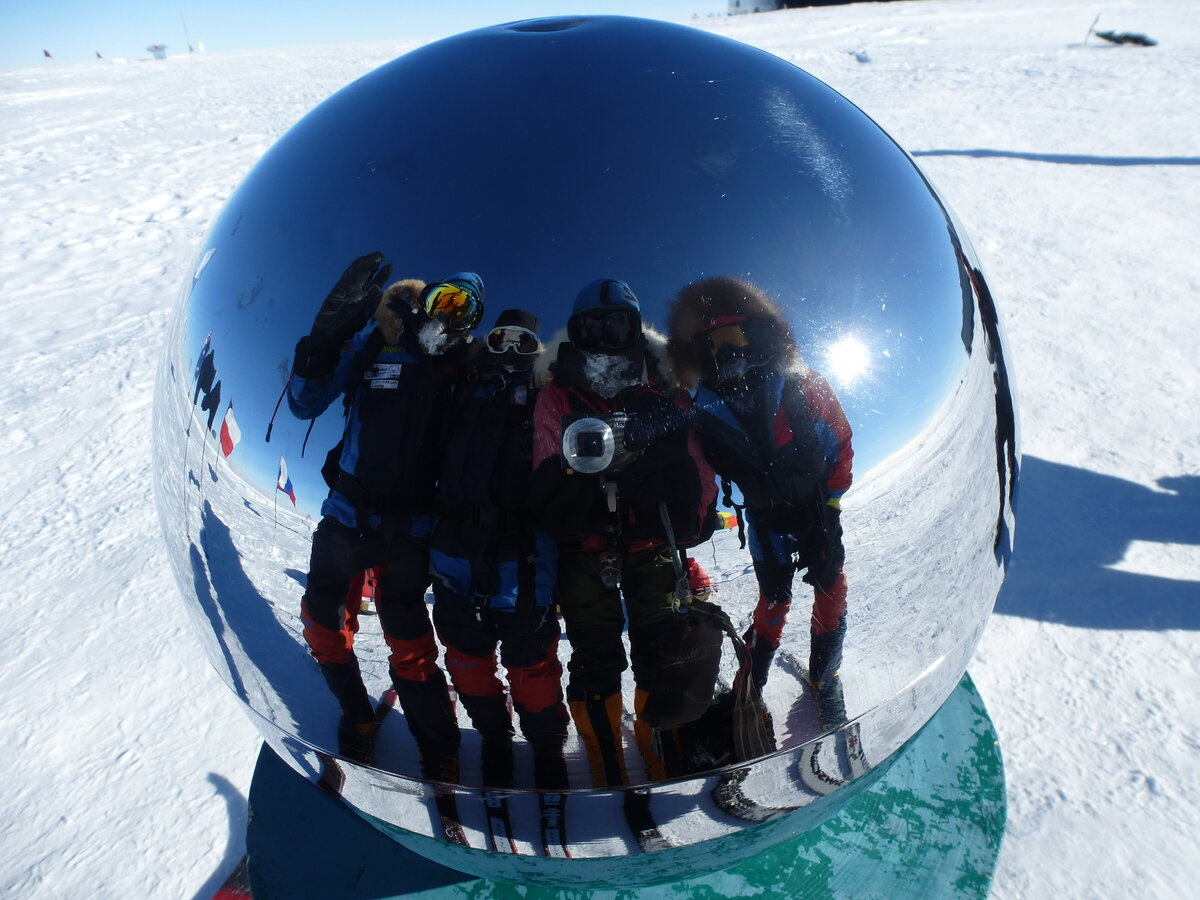 Team photo reflected in the Ceremonial South Pole
