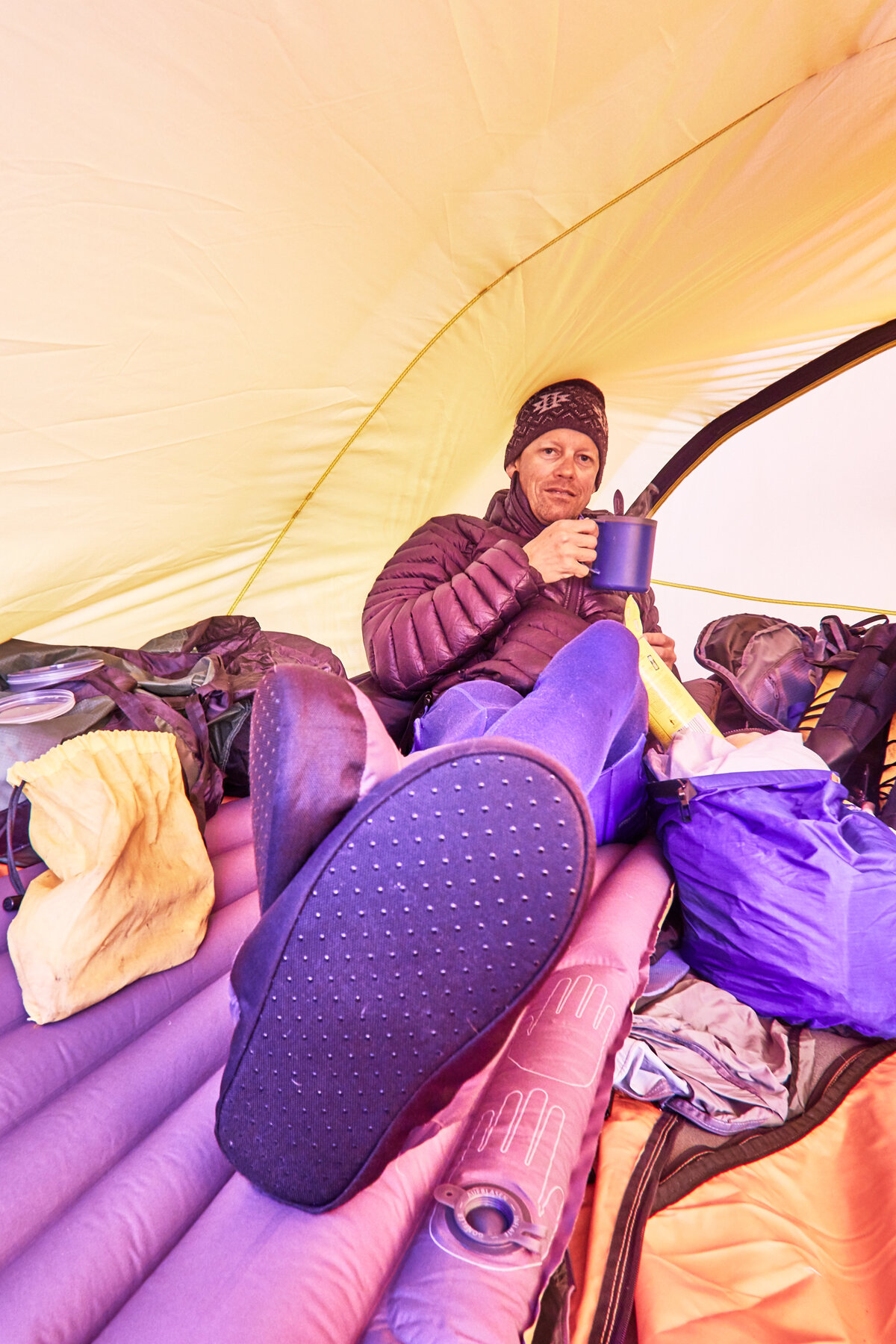 Enjoying a hot drink inside expedition tent