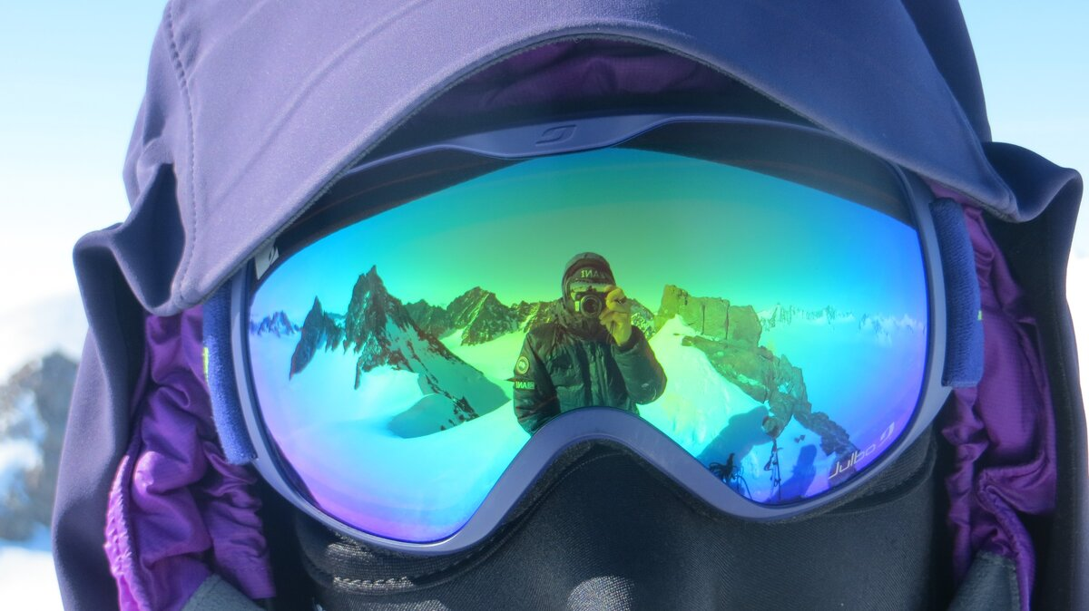 Reflection of peaks in a climber's goggles