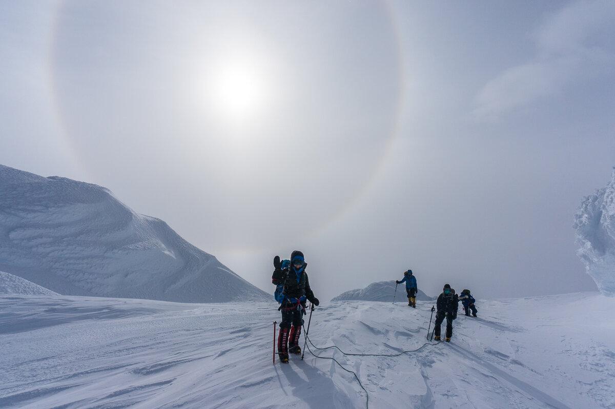 Climbers pass snow features on rim of caldera