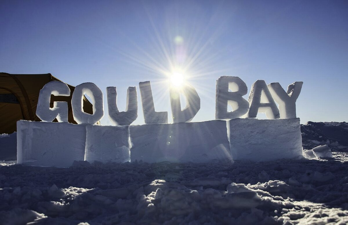 Sun shines on Gould Bay sign, carved out of snow