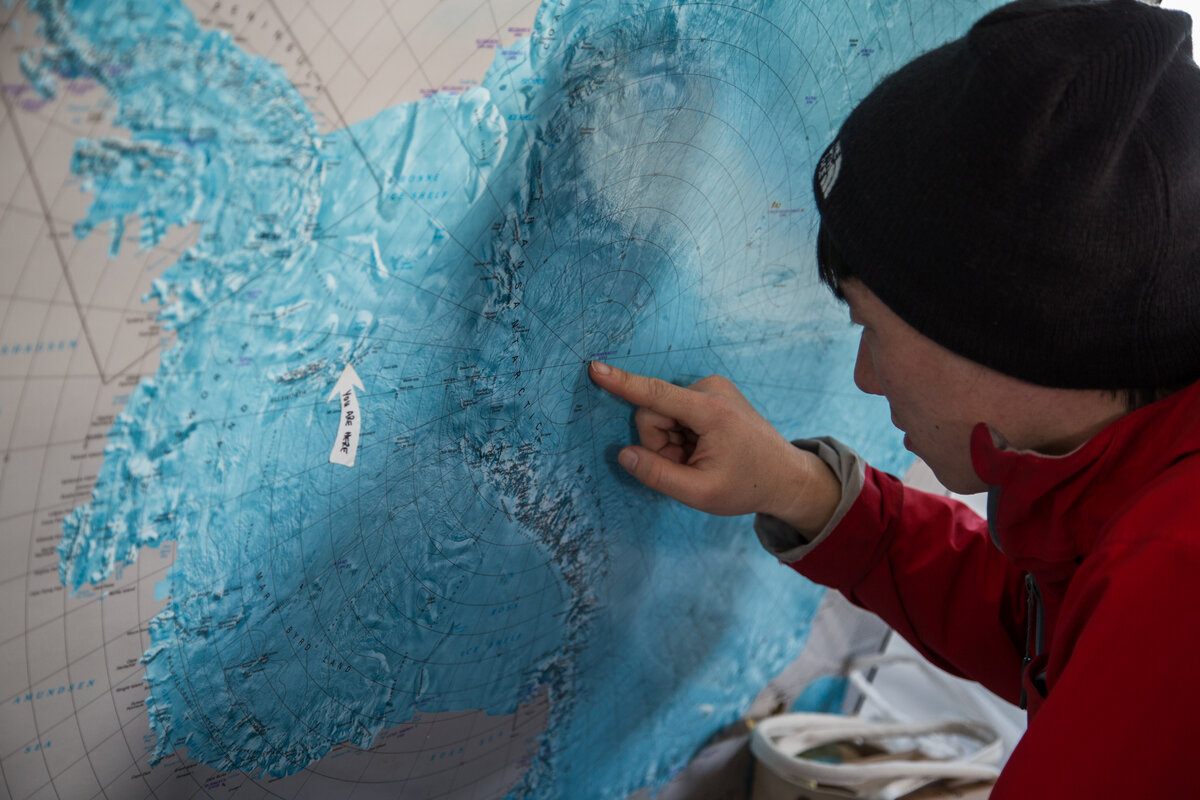 Guest points to the Geographic South Pole on map