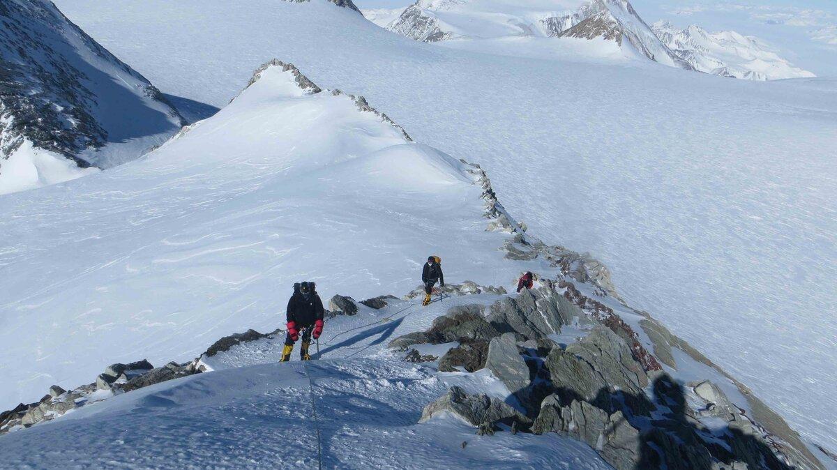 Roped team climbs the summit ridge