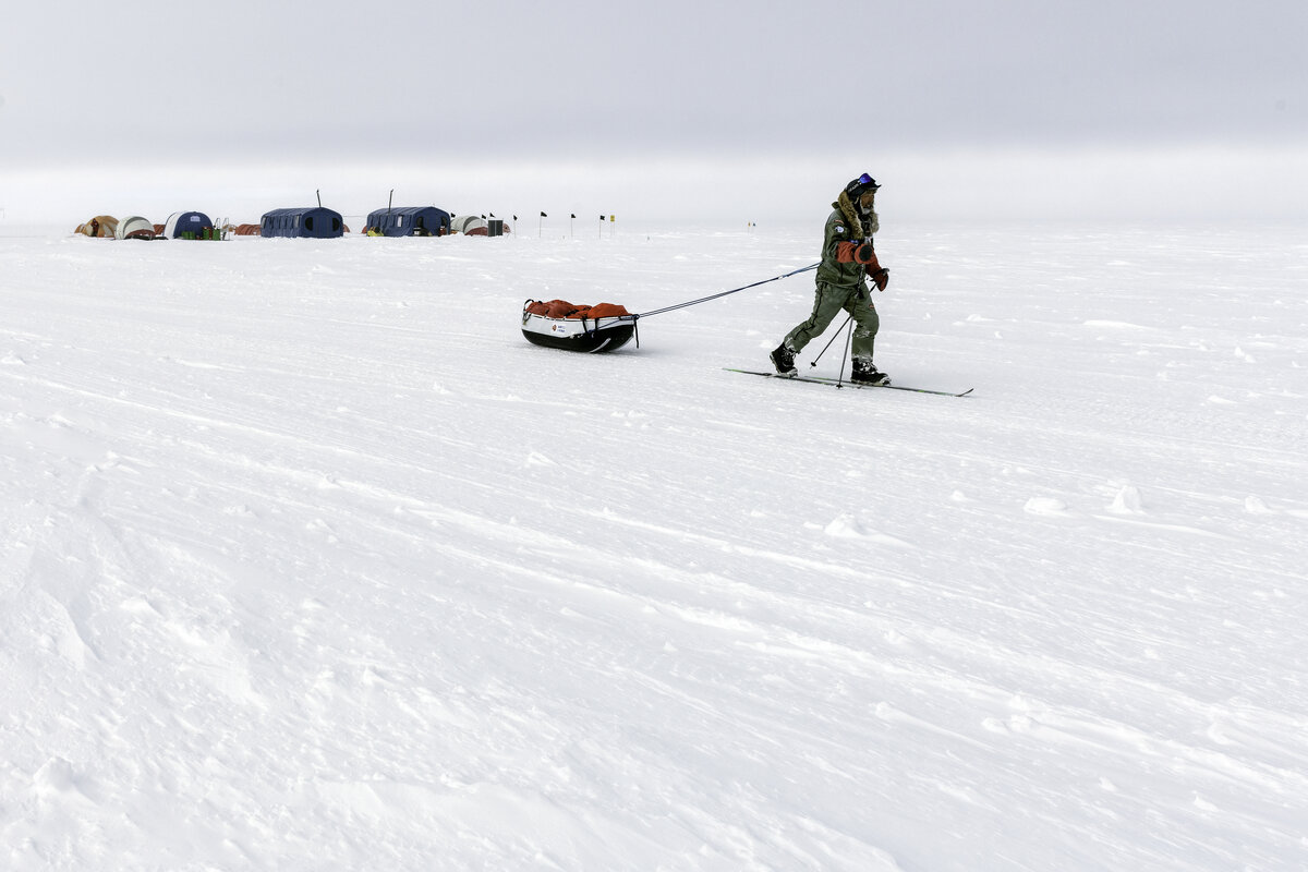 An expeditioner passes camp en route to the Geographic Pole