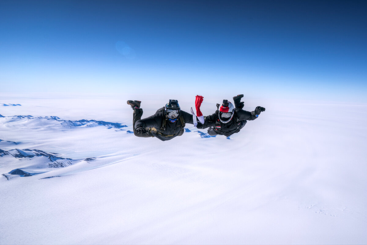 Skydivers prepare to display a flag during free fall