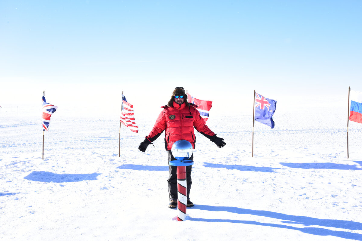 A guest stands behind the Ceremonial South Pole