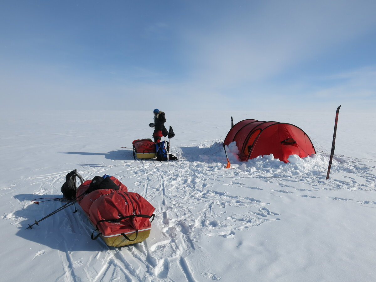 Guest removes gear from sled after setting up camp