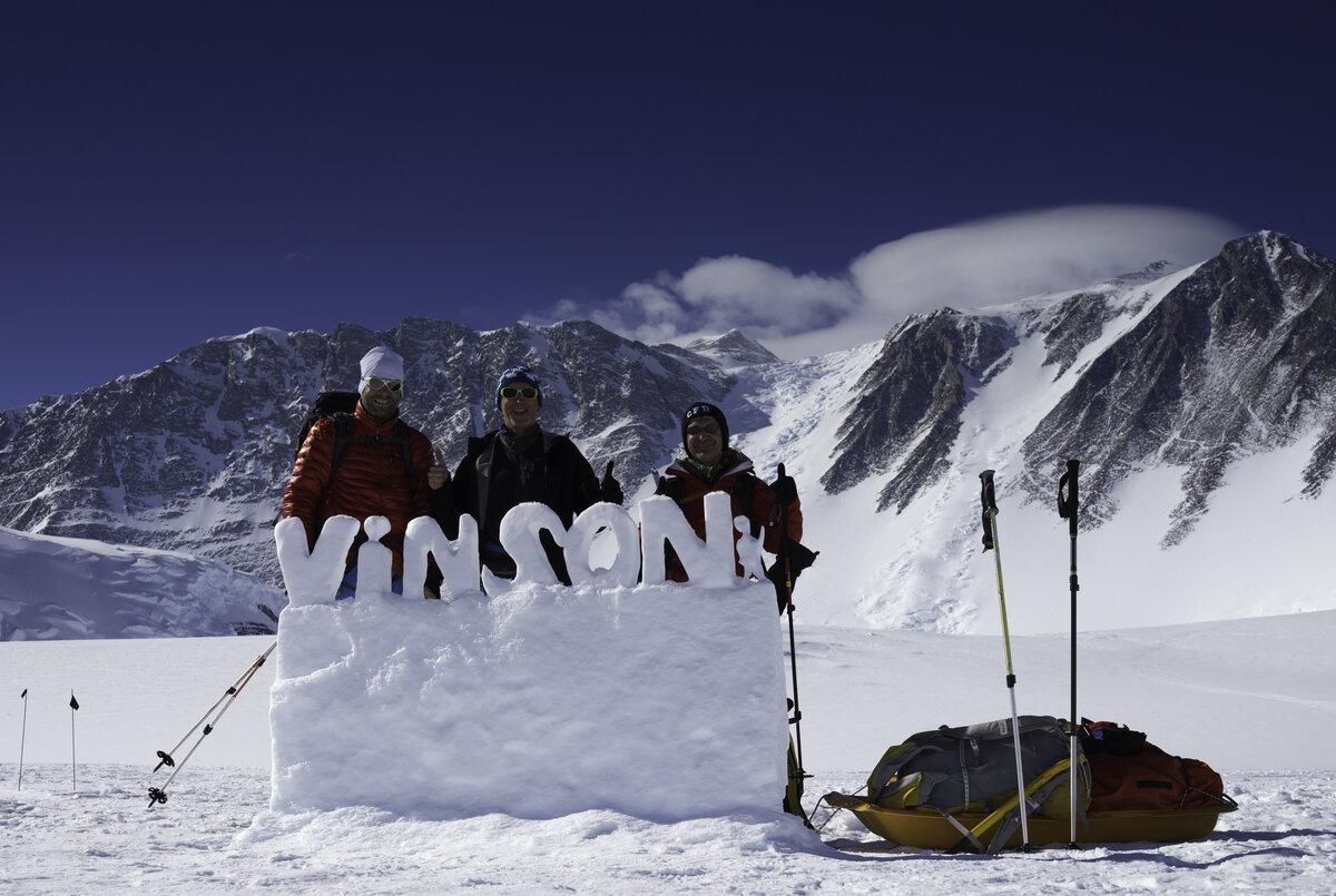 Climbers pose behind Vinson snow sculpture