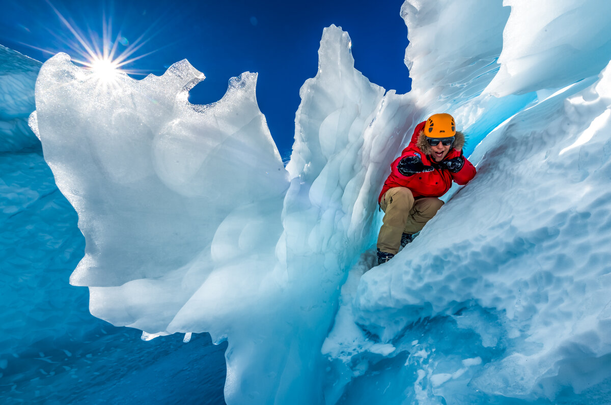 A person 'surfs' between layers of ice and snow at the Drake Icefall